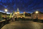 Colorido castillo gótico de praga con la catedral de san nicolás desde el puente de carlos sobre el río moldava en la noche, república checa — Foto de Stock