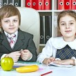 Boy and girl sitting at a table in the schoolchildren with books — Stock Photo #51818813