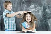 Boy and girl children indulge in school — Stock Photo