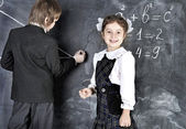 Boy and girl writing on blackboard — Stockfoto