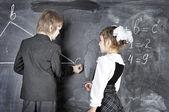 Boy and girl writing on blackboard — Foto Stock