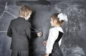 Boy and girl writing on blackboard — Foto de Stock