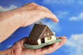 House in the hands of an elderly woman — Stock Photo