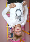 Child hanging upside down on the rings — Stock Photo