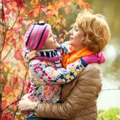 Girl and mother are hiding behind a tree in the autumn park — Stock Photo