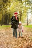 Mom and daughter walk in autumn park — Stock fotografie