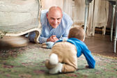 Father playing with baby on the floor at home — Stock Photo