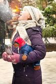 Flickan öppnade sin mun och fångster snöflingor — Stockfoto