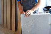 Male carpenter selects a substrate for laminate — Stock Photo