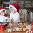 Two cute boys with santa hat, preparing cookies in the kitchen — Stock Photo #56128427
