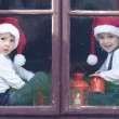 Two cute boys, looking through a window, waiting for Santa — Stock Photo #56129039