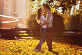 Young couple in love, embracing on sunset in the park — Stock Photo