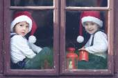 Two cute boys, looking through a window, waiting for Santa — Stock Photo
