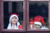 Two cute boys, looking through a window, waiting for Santa — Foto Stock