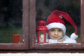 Adorable boy, looking through window, waiting for Santa — Стоковое фото
