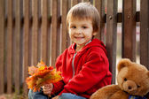 Adorable little boy with teddy bear in the park — Stock Photo
