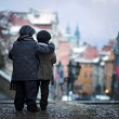 Two kids, standing on a stairs, hugging view of Prague in front — Stock Photo #56246141