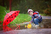 Cute boy with hat, playing with rubber ducks in the park — Stock Photo