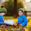 Two boys, reading a book on a lawn in the afternoon — Stock Photo #56485581