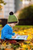 Cute boy, reading a book on a lawn in the afternoon — Foto Stock