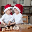 Two cute boys with santa hat, preparing cookies in the kitchen — Stock Photo #57101133