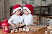 Two cute boys with santa hat, preparing cookies in the kitchen — Foto de Stock