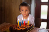 Adorable five year old boy celebrating his birthday and blowing — Stock Photo