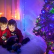 Two boys, playing on tablet at home, next to christmas tree — Stock Photo #57772225