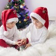 Two cute adorable boys enjoying candies at christmas time — Stock Photo #58693287