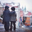 Two kids, standing on a stairs, view of Prague behind them, snow — Stock Photo #58693399