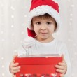 Smiling funny child in Santa red hat holding Christmas gift in h — Photo #58693405