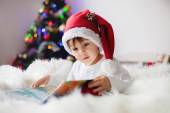 Cute adorable boy reading a book in front of the christmas tree — Stock Photo