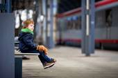 Cute boy, sitting on a bench with teddy bear, looking at a train — Stockfoto