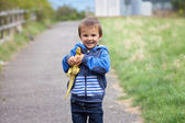 Cute boy, holding a dinosaur — Stock Photo