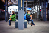 Two boys, sitting in a bench on the railway station — Stock Photo