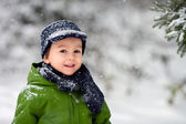 Adorable little boy, blowing snowflakes outside in a snowy day  — Stok fotoğraf