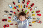 Adorable boy, lying on the ground, toy cars around him  — Stock Photo