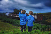Two boy, looking at old steam train — Stock Photo