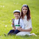 Beautful kid and mom in spring park, flower and present. Mothers — Stock Photo