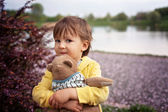 Adorable little boy, holding toy friend in a park — Stock Photo