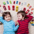Adorable boys, lying on the ground, toy cars around them , looki — Stock Photo #66467173