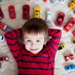 Adorable boy, lying on the ground, toy cars around him , looking — Stock Photo #66467207