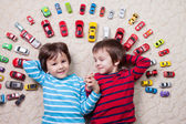 Adorable boys, lying on the ground, toy cars around them , looki — Stock fotografie