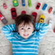 Adorable boy, lying on the ground, toy cars around him , looking — Stock Photo #66472157
