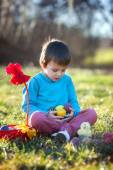 Adorable boy in the park, having fun with colored eggs for Easte — Stock Photo