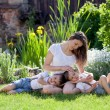 Young mother and her two children, boys, sitting on a lawn, tend — Stock Photo #67863067