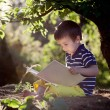 Beautiful kid boy, reading a book in garden, sitting next to a t — Stock Photo #67863081