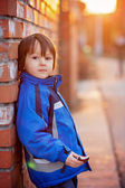 Adorable little boy, next to brick wall, eating chocolate bar on — Stockfoto