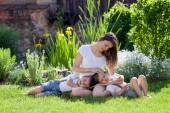 Young mother and her two children, boys, sitting on a lawn, tend — Stock Photo