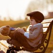 Adorable little boy with his teddy bear friend in the park — Stock Photo #69204603